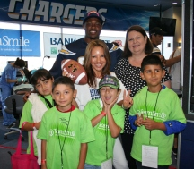 Teachers Amalia Lopez and Denise Lunsford share a smile with students and Chargers player Marcus Gilchrist.